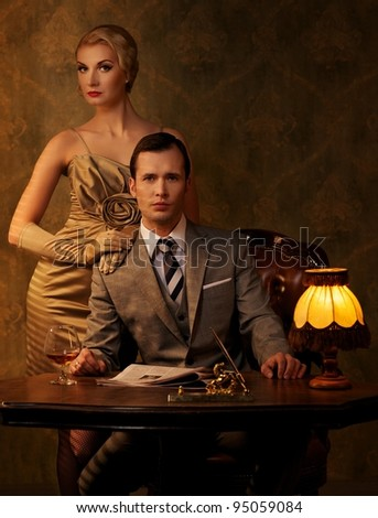 Retro couple sitting behind table.