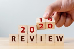 2020 review concept. Hand flip wood cube change year 2019 to 2020 and the word REVIEW on wooden block on wood table