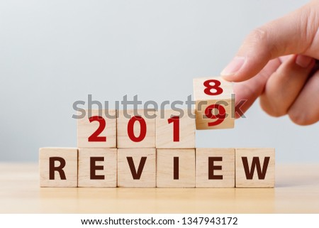 2019 review concept. Hand flip wood cube change year 2018 to 2019 and the word REVIEW on wooden block on wood table #1347943172