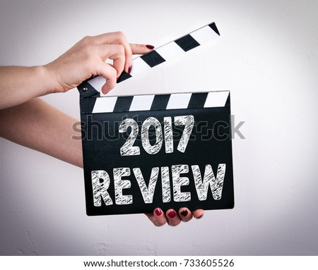 2017 review. Female hands holding movie clapper  #733605526