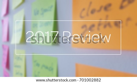 2017 Review, superimposed on a blurred image of sticky notes on a whiteboard #701002882