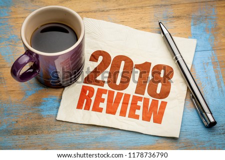 2018 review text on a napkin with a cup of coffee #1178736790