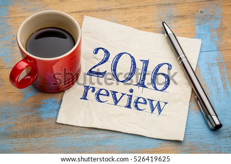 2016 review text on a napkin with coffee against grunge wood desk