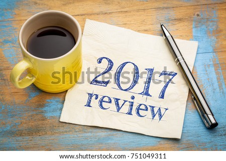 2017 review text on a napkin with coffee against grunge wood desk #751049311