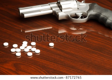 .357 revolver laying on wooden surface with drugs
