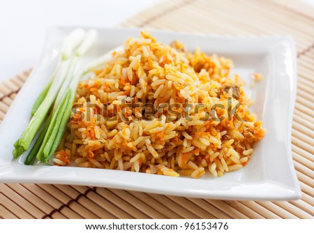 Rice with green onions and brown bread on a white square plate.  Isolated on white