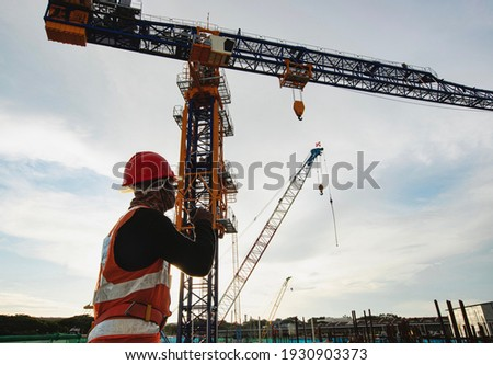 Rigger signal crane at construction site with walkie;talkie