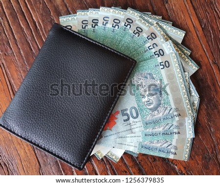 50 ringgit Malaysian banknotes out of black wallet.
