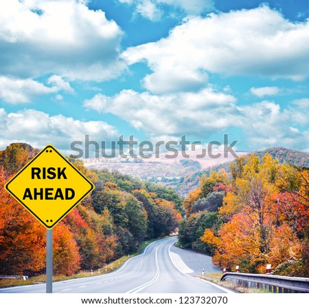 """""""RISK AHEAD"""" sign against road - Business concept"""