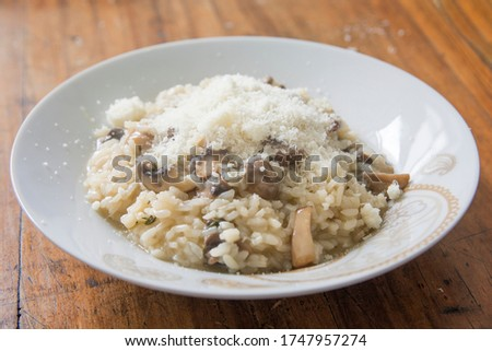 'Risotto ai funghi',cooked rice dish with slices of Common Mushrooms with Parmesan cheese, in a white bowl Foto d'archivio ©