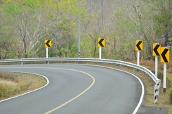 Road signs warn of a sharp turn on a narrow road.
