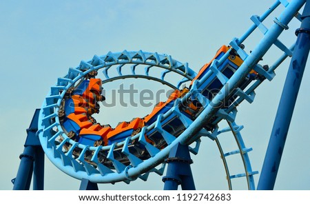 Roller coaster  ride filled  with thrill seekers doing loop.