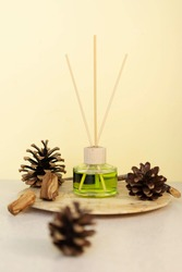 room air freshener on a wooden decorative plate with fragments of wood and pine cones. Woody scent concept for home