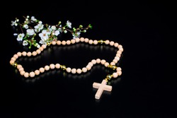 Rosary beads  on black background. white spring flowers