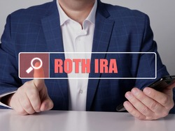 ROTH IRA individual retirement account phrase on the screen. Bookkeeping clerk use cell technologies at office. Concept search and ROTH IRA individual retirement account.