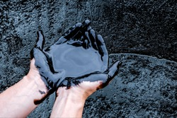 rude oil surface background textured. Mineral oil in the hands of man. Caucasian hands cupped with black rock-oil