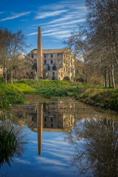 ruined textile factory in the forest. River reflection
