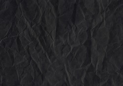 rumpled dark black matte paper. Texture of old dark black paper closeup.