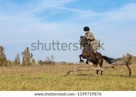 07.10.2018 Russia, Moscow. Caucasian man in a national military suit of last years astride black horses jumps through an obstacle in the field #1199719876