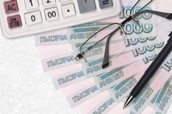 1000 russian rubles bills fan and calculator with glasses and pen. Business loan or tax payment season concept
