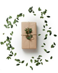 rustical simple gift decorated with twine and a green boxwood sprig. isolated on white background and leaves. flatlay. vertical