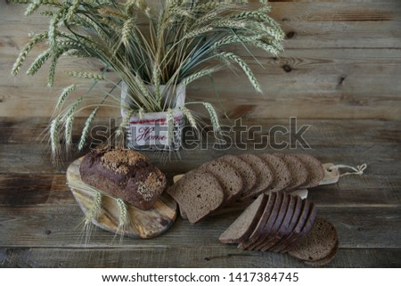 rye bread and rye ears in a basket with the inscription HOME on a wooden rustic background with copy space for text #1417384745