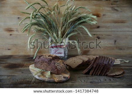 rye bread and rye ears in a basket with the inscription HOME on a wooden rustic background with copy space for text #1417384748