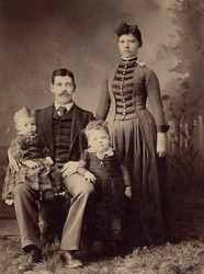 1800s Antique family portrait depicting a mother and father and their two children.
