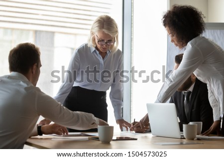50s business woman lead group meeting with multi-ethnic staff in boardroom, diverse colleagues working together planning at morning briefing preparing report presentation for client, teamwork concept