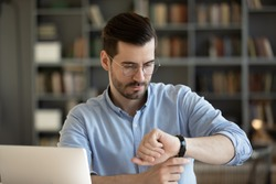 35s businessman wear glasses looks at wristwatch checks time waits for client who is late while sitting at work place desk with laptop. Concept of business, time is money, punctuality and timekeeping