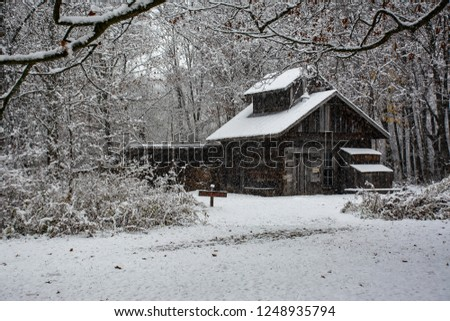 1870s cabin with snow falling and fresh snow on ground surrounded by woods.