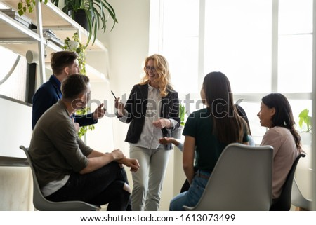 50s company owner and young multiracial staff taking part in corporate training new profitable project discussion, educational process, have fun at break, mentoring, teambuilding in co-working concept