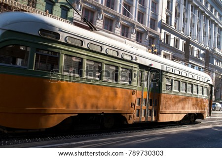 1950s Looking Passenger Commuter Street Car Traveling on Electronic Rail System Along Metropolitan City Downtown Street in Busy Congested Business District during Daytime with Buildings in Background #789730303