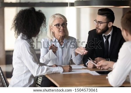 60s mature team leader company owner giving instructions telling about corporate goals and plans to multi-ethnic young staff member during group meeting in office boardroom, mentoring coaching concept
