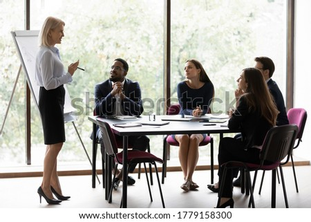 50s old corporate trainer provide knowledge to young professionals company staff multi ethnic people take part at seminar educational meeting sit in boardroom. Workshop flip chart presentation concept