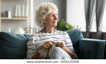 70s old woman sit on sofa, distracted from hand knitting grandmother look out window enjoy scenery at sunny weather reduces stress, take break without feeling useless, hobby free time activity concept