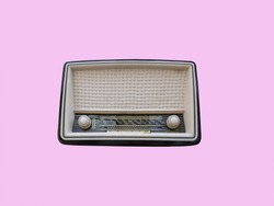 1950's retro vintage radio with turning knobs and speaker on a pastel pink background