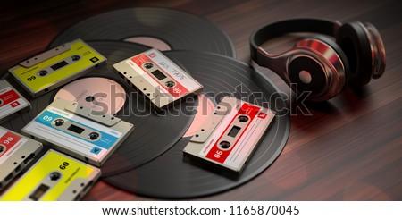 1970s-1980s party music. Vintage audio cassettes, vinyl records and dj headphones, wooden background. 3d illustration