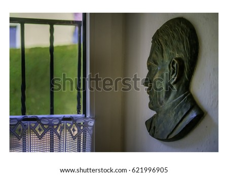 1930s/1940s wall plaque of Adolf Hitler appearing to gaze out of  an iron-barred window.