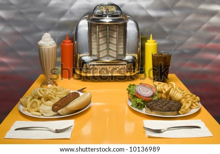 1950's style diner table with juke box, malt, cola, hot dog and
