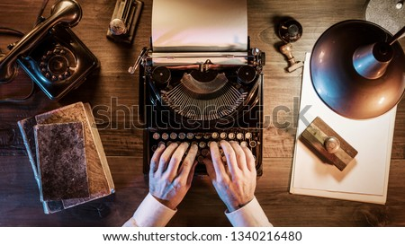 1950s style journalist working in his office at night, he is typing with a vintage typewriter, flat lay desktop Stock photo ©