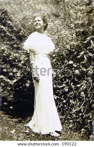 1930's vintage black and white soft focus. Young woman walking in long white gown.