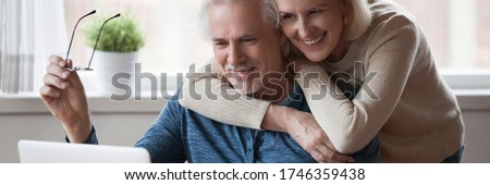60s wife hug husband spouses looking at pc screen read good news. Make videocall talk with grownup children, receive great offer eyewear sale concept. Horizontal photo banner for website header design Stockfoto ©