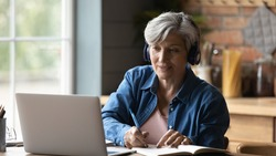 60s woman sit at table wear headphones take notes gain new skills use laptop and internet resources, on-line services. Video call event, modern tech, counselling, receive information remotely concept