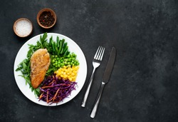 salad of chicken breast, arugula, red cabbage, carrots, corn, green peas, green beans in a white plate on a stone background with copy space for your text