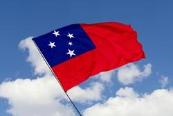 Samoa flag isolated on sky background. Close up waving flag of Samoa. Concept of Samoan.