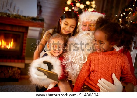 Santa Claus sharing smart phone with children in Christmas atmosphere