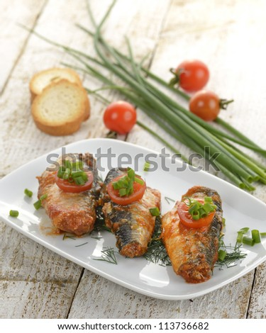 Sardines In Tomato Sauce On A White Dish - stock photo