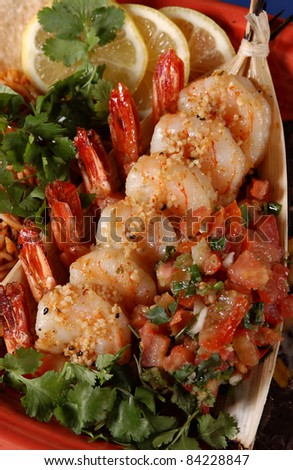 7 sauteed shrimp topped with minced garlic, alongside salsa and rice, garnished with cilantro and lemon.