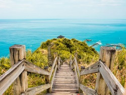 Scenery of Taiwan. Lookout symmetrical view of wooden pathway on the greenery mountain and turquoise ocean. Amazing top view on the top of the hill. Composition of symmetrical fence.